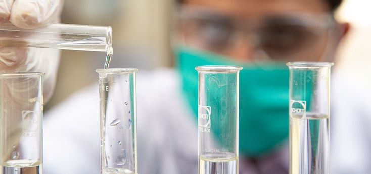Photograph of a male scientist pouring liquid into test tubes